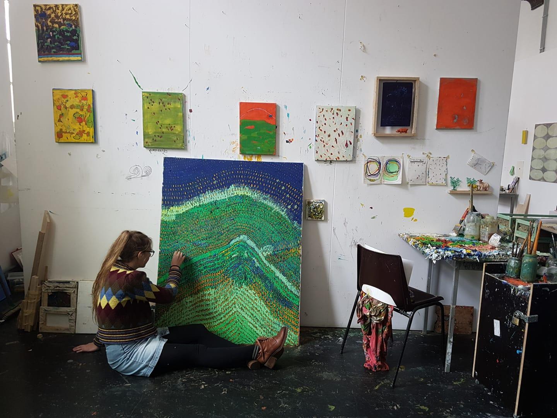 Svelte Thys knielend aan het werk aan landschappelijk schilderij