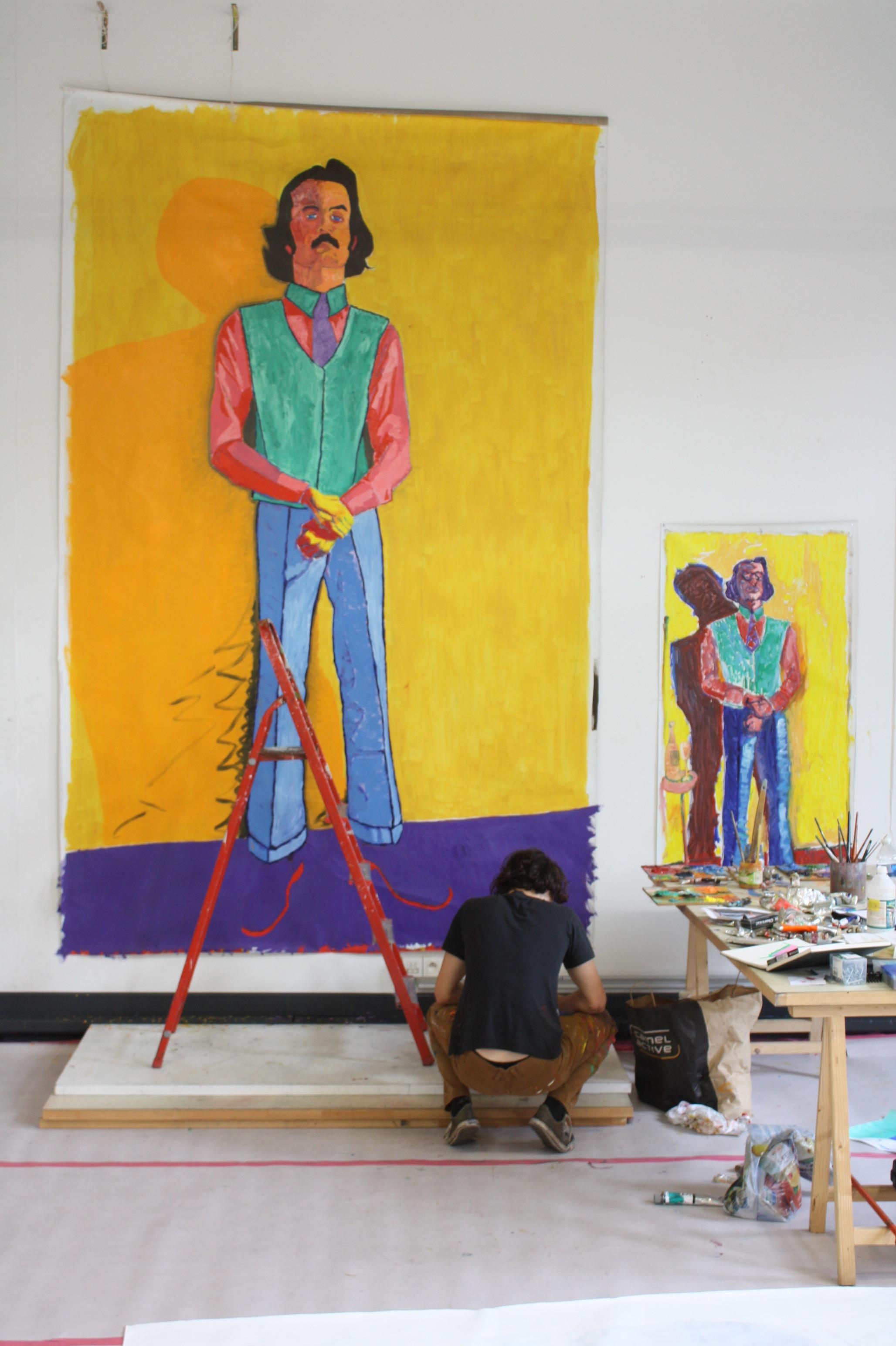 Vic aan het werk aan een metersgroot zelfportret, staand met felle kleuren.