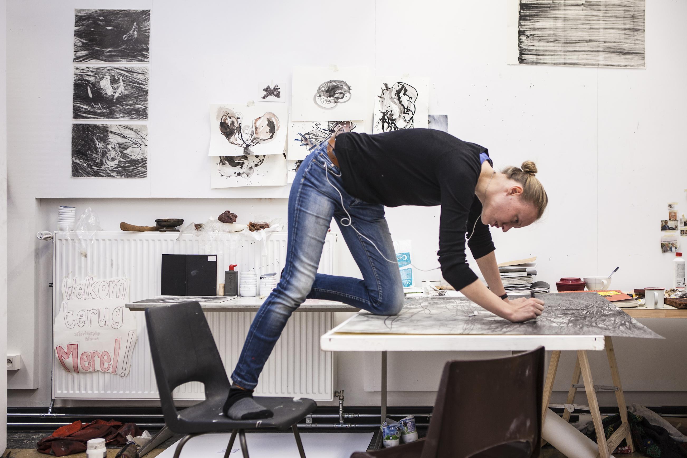 merel Vandecasteele aan het werk zittend op haar werktafel.