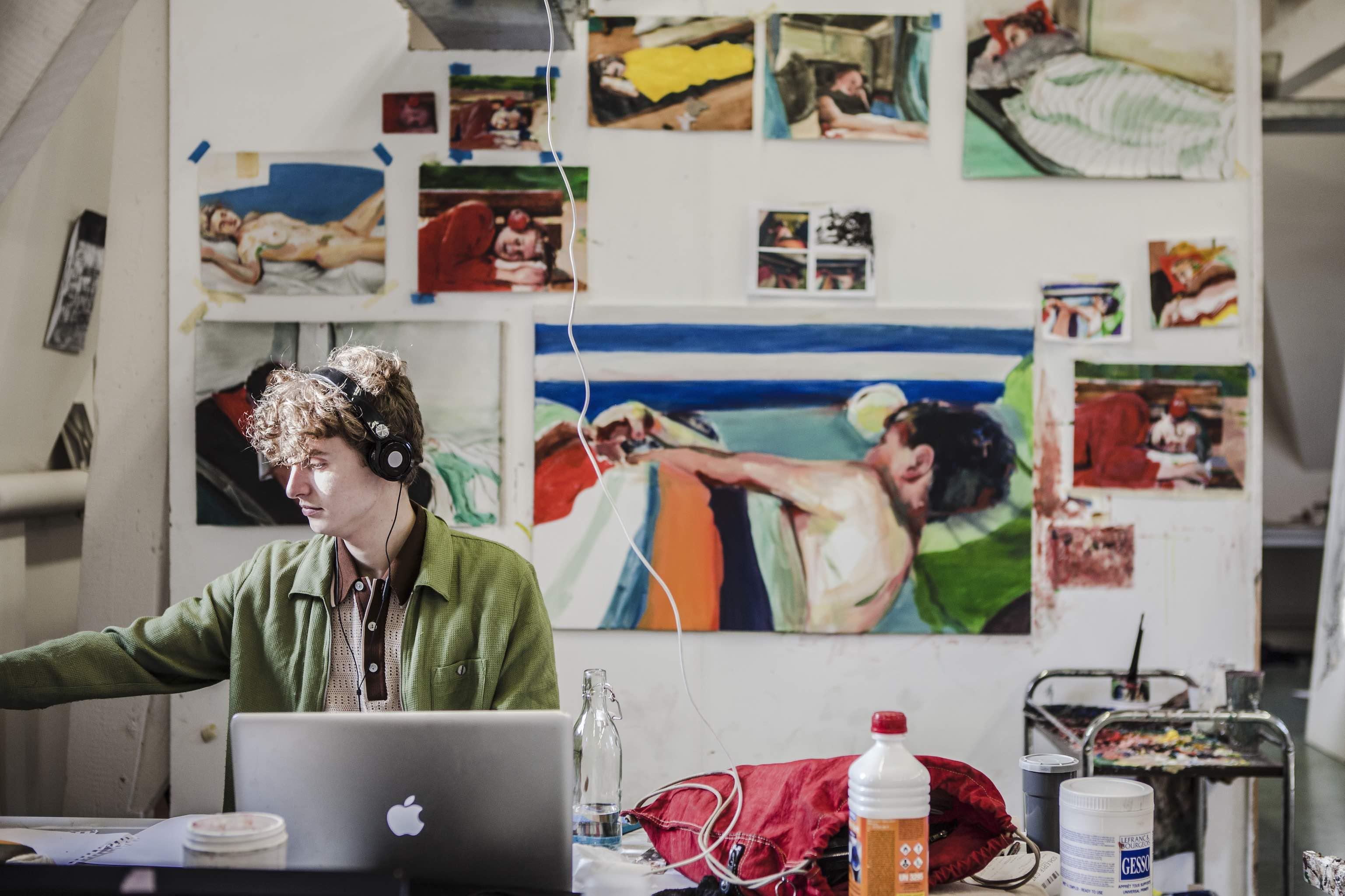Pieter zitten met koptelefoon aan het werk voor muur met schilderijen van liggende mensen